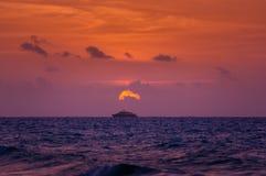 Barco en el océano en la puesta del sol o la salida del sol Fotografía de archivo