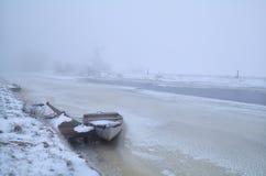Barco en el río congelado en día de invierno de niebla Foto de archivo