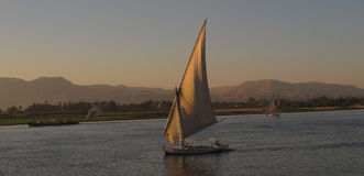 Barco en el río Nilo en la puesta del sol Imagen de archivo libre de regalías