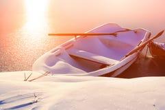 Barco en la nieve en el amanecer en el río en invierno Imagenes de archivo