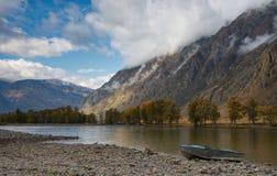 Barco en la orilla Autumn Mountain Landscape With un River Valley, un cielo nublado hermoso y un barco del aluminio en una orilla fotos de archivo libres de regalías