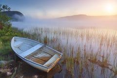Barco en la orilla de un lago brumoso en una mañana del verano imagenes de archivo