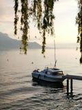 Barco en la orilla del lago Lemán durante la puesta del sol foto de archivo