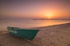 Barco en la playa en la puesta del sol Imágenes de archivo libres de regalías