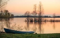 Barco en la puesta del sol en el lago Fotos de archivo