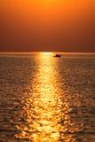 Barco en la puesta del sol en el mar con reflexiones y nubes Imagen de archivo libre de regalías
