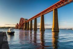 Barco en la puesta del sol en un puente viejo del metal en Escocia Imágenes de archivo libres de regalías