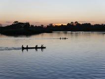 Barco en luz de la puesta del sol de la tarde del río Imagen de archivo