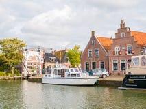 Barco en puerto, puente y casas en la ciudad vieja de Makkum, Friesl imagen de archivo libre de regalías