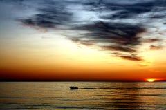 Barco en puesta del sol Foto de archivo libre de regalías
