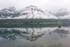 Barco en un lago con las montañas y las nubes en un fondo con la reflexión en el agua, Noruega Fotografía de archivo