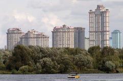 Barco en un río en altos edificios delanteros Imagen de archivo libre de regalías