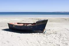 Barco en una playa aislada en Suráfrica Imagenes de archivo