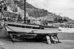 Barco encallado con en el fondo Amalfi y su puerto, Campania, Italia fotografía de archivo