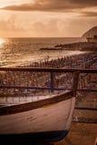 Barco encallado en puesta del sol sobre la playa con los paraguas Imagenes de archivo