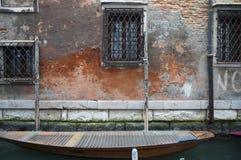 Barco entrado a uma parede da casa em um canal em Veneza, Itália Foto de Stock