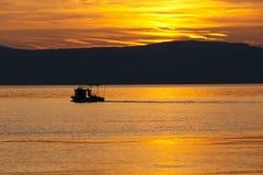 Barco flotante durante puesta del sol Foto de archivo libre de regalías