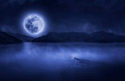 Barco funcionado con a la Luna Llena Imágenes de archivo libres de regalías