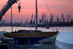 Barco, grúas, muelle y cielo purpurino Fotos de archivo libres de regalías