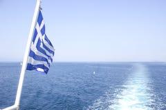 Barco griego con la bandera en el mar Fotos de archivo libres de regalías