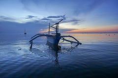 Barco hermoso en la playa de Lovina, Bali durante salida del sol con el delfín Foto de archivo libre de regalías