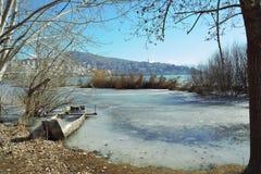 Barco hundido mitad en el lago congelado Fotos de archivo