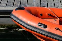 Barco inflable anaranjado amarrado cerca del embarcadero Fotografía de archivo libre de regalías