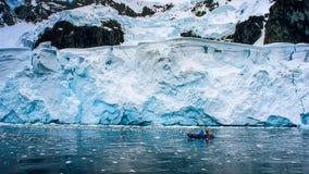 Barco inflable con el explorador para la exploración antártica fotos de archivo