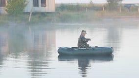 Barco inflable con un pescador de sexo masculino en un lago en la niebla El sol se levanta sobre las nubes del mar y del oro metrajes