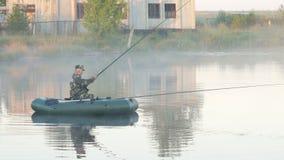 Barco inflable con un pescador de sexo masculino en un lago en la niebla El sol se levanta sobre las nubes del mar y del oro almacen de metraje de vídeo
