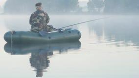 Barco inflable con un pescador de sexo masculino en un lago en la niebla El sol se levanta sobre las nubes del mar y del oro almacen de video