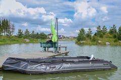 Barco inflable en el embarcadero de madera en el lago Foto de archivo libre de regalías