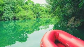 Barco inflable rojo y las aguas verdes del río de Formoso fotografía de archivo
