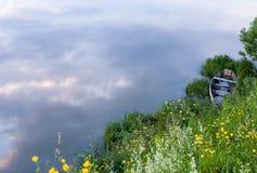 Barco inundado abandonado en la hierba en la orilla del río Imagen de archivo