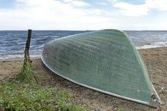 Barco invertido en la orilla de un lago grande foto de archivo libre de regalías