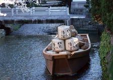 Barco japonês com bens em um rio amarrado ao banco com um fundo da corda imagem de stock royalty free