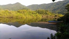 Barco, lago y montañas Cielo, agua y sombras Foto de archivo