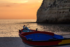 Barco a lo largo de la costa en la puesta del sol Imagen de archivo libre de regalías