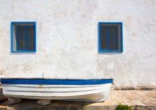 Barco mediterráneo y pared blanqueada en blanco y azul Fotografía de archivo
