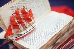 Barco minúsculo sobre la composición de la página de un libro abierto Fotos de archivo libres de regalías