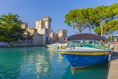 Barco a motor no porto Sirmione na frente do castello Scaligero no lago Garda foto de stock royalty free