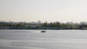 Barco a motor rápido que flutua através do rio O lado segue o tiro Barco a motor no rio da cidade vídeos de arquivo