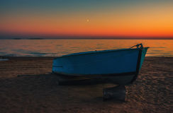 Barco na praia no fundo do por do sol Fotografia de Stock Royalty Free