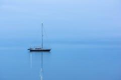 Barco negro solo en el océano antes de la salida del sol Imagen de archivo libre de regalías