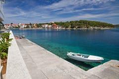 Barco no mar, vila no fundo Imagem de Stock Royalty Free
