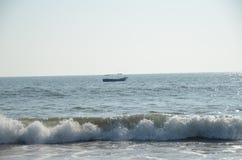 Barco no oceano com as ondas que rolam dentro Imagens de Stock