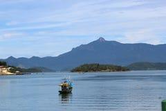 Barco, oceano e cume em dos Reis de Angra, Brasil Imagens de Stock