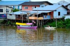 Barco púrpura y amarillo colorido en el río de Sarawak por el pueblo Kuching Malasia del kampong fotografía de archivo