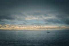 Barco perdido en un día cambiante del océano foto de archivo