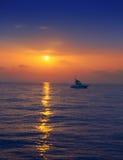 Barco pesquero en horizonte en salida del sol de la puesta del sol en el mar Imagenes de archivo